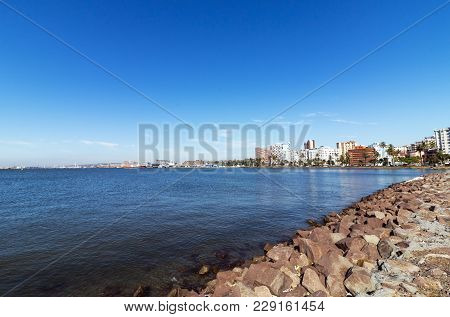 Rock Bank And High Tide In Durban Harbor Against Blue Sky And Durban City Skyline In South Africa