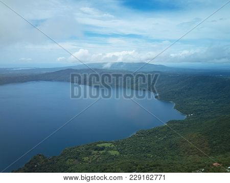 Aerial view on Apoyo lagoon in Nicaragua. Blue lagoon water drone view poster