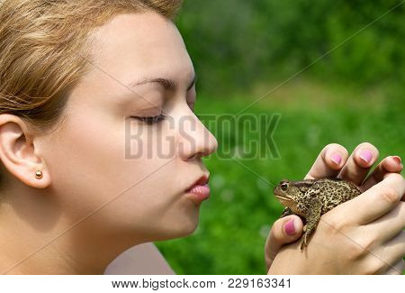 Young Woman Kissing A Toad In Her Hands