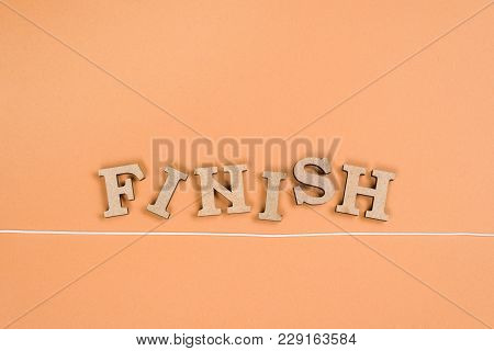 Word Finish With Wooden Letters And Finish Line On An Orange Background.