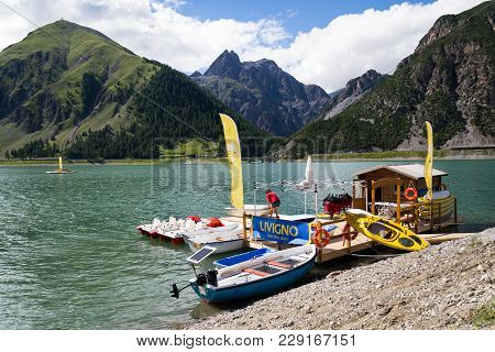 Livigno, Italy - August 1: Woman On Wooden Pier With Boats, Kayaks And Pedal Boats On Lago Di Livign