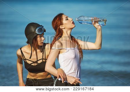 Young Woman Drinking Water On A Hot Day . Two Girls On A Hot Summer Day