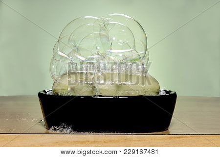 Green Soap With Bubbles On A Black Soap Dish