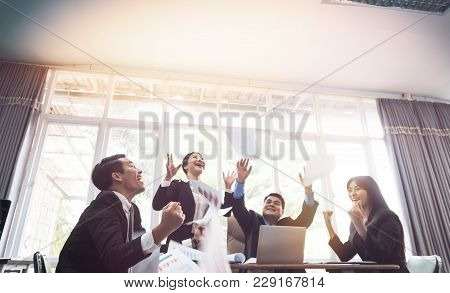 Group Of Business Throwing Sheets For Work After Finishing Work In Meeting Room. Cheerful And Happin