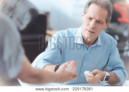 Will It Help. Unhappy Serious Good Looking Man Sitting At The Table And Taking A Bottle Of Painkille
