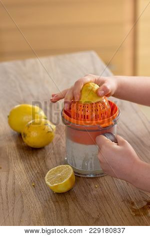 Little Girl Squeezing A Lemon