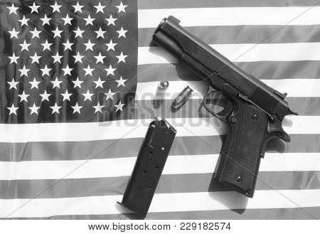 1911 hand gun, clip and extra bullets on an American flag. 2nd amendment rights concept.