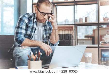 Working Process. Attentive Male Person Bowing His Head And Looking At Screen Of His Laptop While Tal