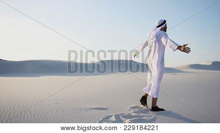 Joyful Male Arabian Sheikh Muslim Walks Through White Sand Deser