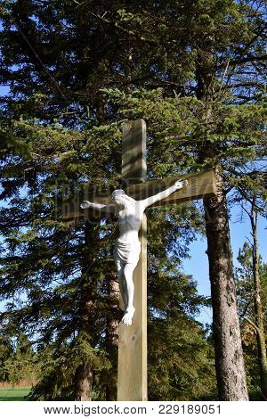 A Statue Of Jesus Christ Is Nailed To A Cross In A Catholic Cemetery