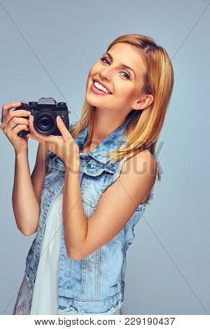 Smiling Blond Female Holds Compact Digital Photo Camera, Isolated On Grey Background.