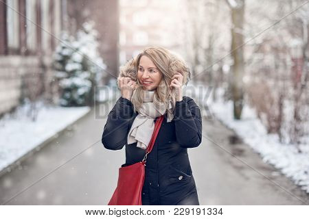 Smiling Young Woman Walking Along A Snowy Road In Winter Holding The Fur Trim On Her Jacket Looking