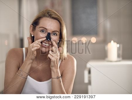 Attractive Middle-aged Blond Woman Applying An Anti-aging Face Mask To Her Nose In A Bathroom With B