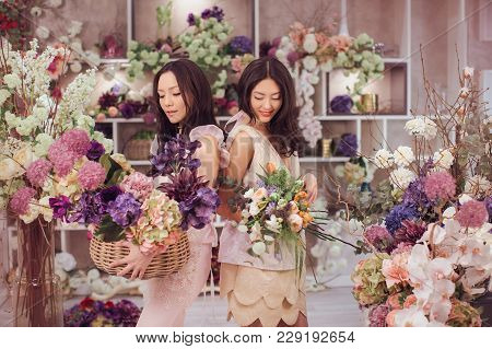 Beautiful Asian Florist Girls Holding Bouquet And Basket Of Flowers For Sale Against Floral Bokeh Ba