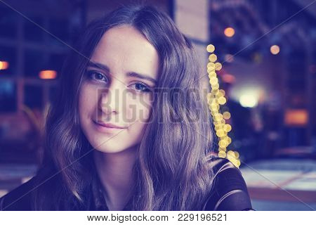 Handsome Girl Is Sitting In The Cafe. She Has Big Brown Romantic Eyes. With Nice Brown Long Hair. We