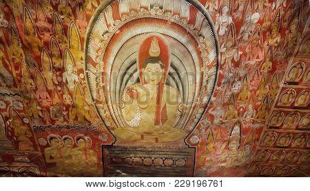 Dambulla, Sri Lanka - Jan 8, 2018: Looking Happy Gautama Buddha On Fresco With Monks On Ancient Ceil