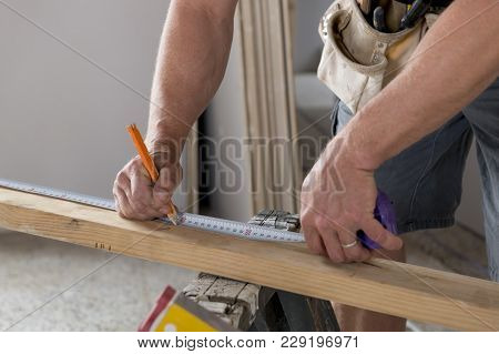 Close Up Male Constructor Carpenter Or Builder Hands Detail Working And Measuring Wood In Industrial