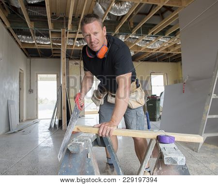 Attractive And Confident Constructor Carpenter Or Builder Man Working Cutting Wood With Manual Saw A