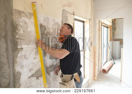 Portrait Of Young Attractive Builder Man Working Confident Measuring And Leveling Wall With Building