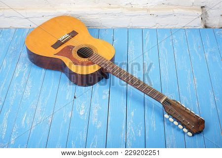 Musical Instrument - Vintage Twelve-string Acoustic Guitar On A Brick Background And Blue Wooden Flo