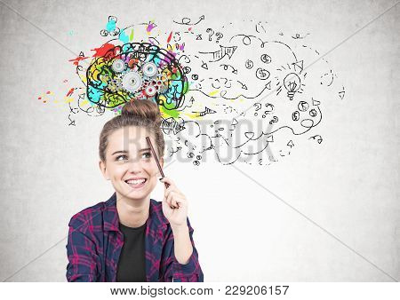 Smiling Teen Girl In A Checkered Shirt Is Sitting With A Pencil Near Her Forehead And Thinking. She