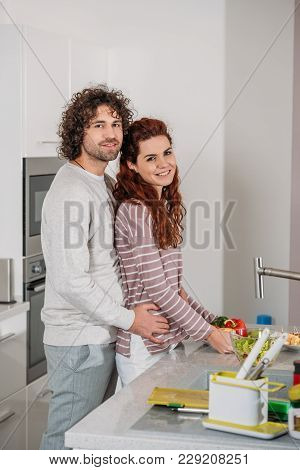 Boyfriend Hugging Girlfriend From Back At Kitchen And They Looking At Camera