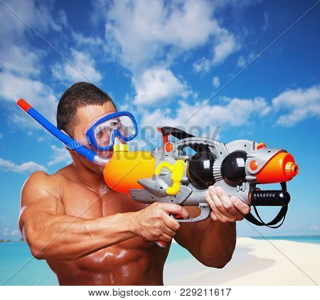 Portrait Of Muscular Male On A Beach With Hight Pressure Water Toy Gun.