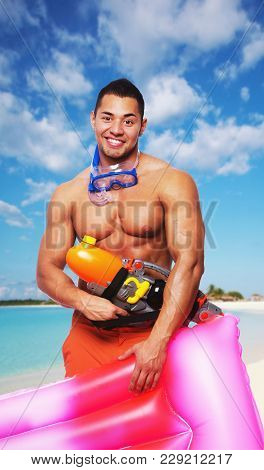 Smiling Shirtless Muscular Male Holding Pink Water Matress And Water Hight Pressure Gun Over Sea Coa