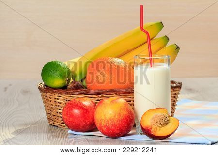 Glass Of Delicious Yogurt With Mint And Fresh Strawberries, Banana, Lime, Nectarine In Wicker Basket