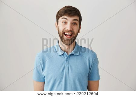 So Happy To See You. Studio Shot Of Enthusiastic Funny Male Employee Smiling Cheerfully And Lifting