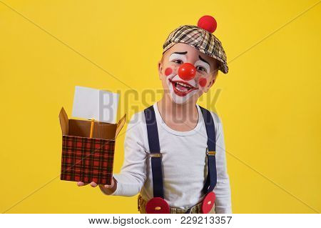Funny Kid Clown Isolated On Yellow Background. Beautiful Playful Portrait Child Boy Jester In Makeup