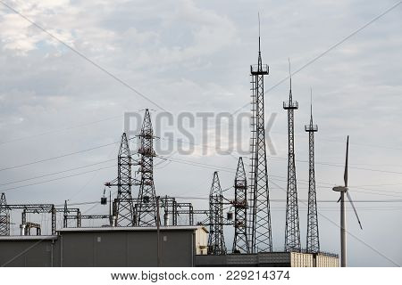 Electricity Transmission Pylons Against Cloudy Sky Background. High Voltage Towers.