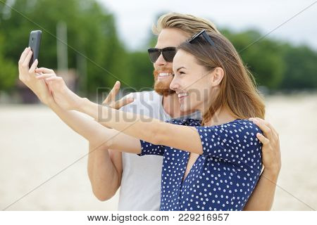 Two Lovers Making A Selfie Photo On A Beach
