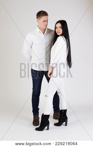 Guy With The Girl On A White Background.a Man With A Sporting Body And A Woman With Long Black Hair