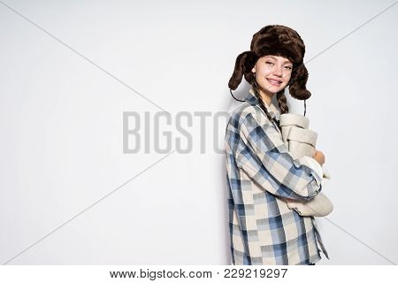 Happy Young Girl From Russia In A Warm Fur Hat Prepares For A Cold Winter, Holds Gray Felt Boots
