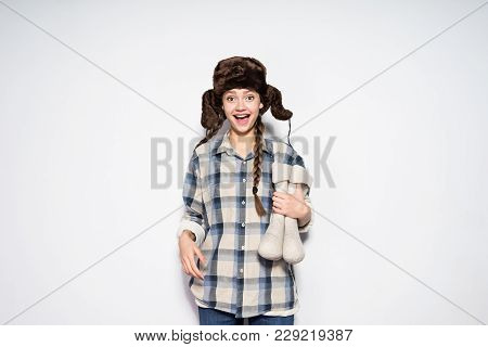 Happy Young Girl From Russia In A Warm Fur Hat Prepares For A Cold Winter, Holds A Gray Felt Boots,