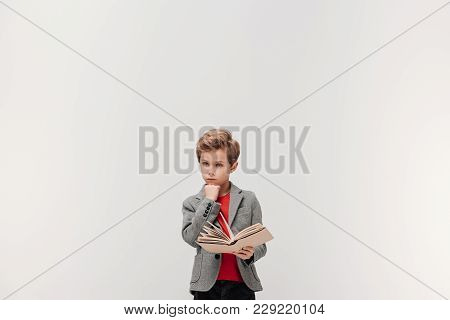 Thoughtful Little Schoolboy With Book Isolated On Grey