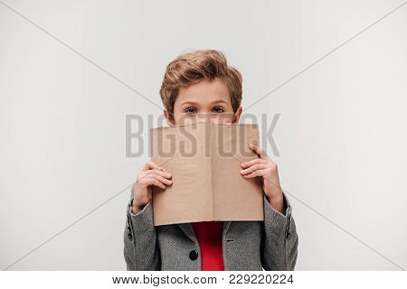 Stylish Little Schoolboy Covering Face With Book Isolated On Grey