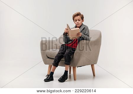 Focused Little Schoolboy Reading Book In Armchair