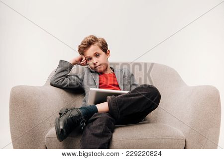 Stylish Little Boy With Tablet Sitting In Armchair And Looking At Camera Isolated On Grey