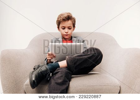 Serious Little Boy Using Tablet  While Sitting In Armchair Isolated On Grey