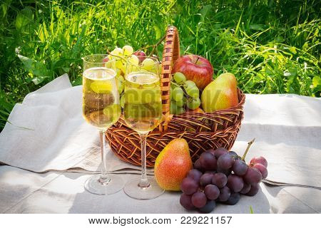 Glasses Of Champagne And Basket With Fruits On Grass