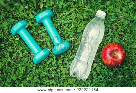 Dumbbells, Apple And Bottle With Water On Grass. Concept Of Healthy Lifestyle.