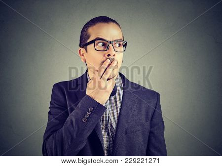 Young Nervous Man In Suit Looking Away Having Difficult And Awkward Situation.