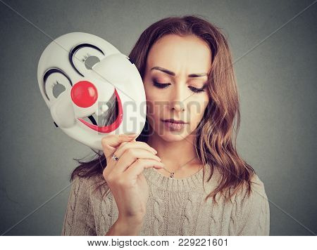Young Upset Woman Covering Personality With Happy Clown Mask On Gray Background.