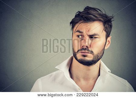 Handsome Bearded Man In White Shirt Looking Away With Suspicion On Gray Background.