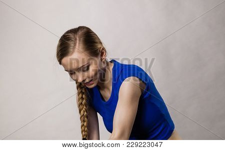 Blonde Young Woman Having Braided Hairstyle Wearing Sports Wear Relaxing After Training. Gray Backgr