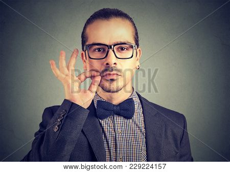 Confident Serious Man Zipping Mouth Keeping Confidential Information While Looking At Camera.
