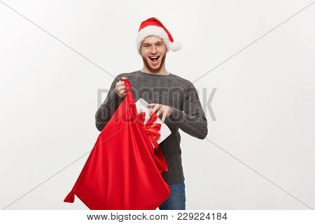 Christmas Concept - Young Happy Beard Man Excite With Big Present In Santa Bag