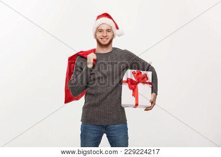Christmas Concept - Young Happy Beard Man Holding Santa Bag And White Present